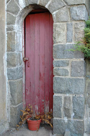 Red wooden door in the wall of a stone castle Imagens