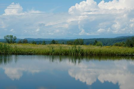 Reflection of clouds in a quiet roadside pond near Paris, Maine, with White Mountains in the distance Imagens