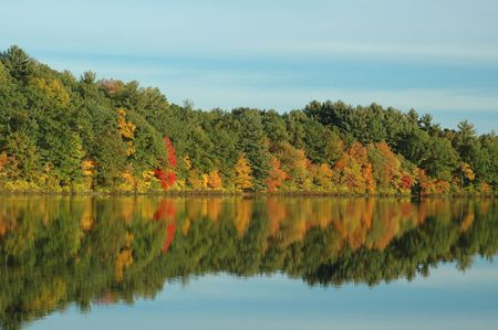 Foliage reflected on Johnsons Pond in Boxford, MA, on a clear fall day Imagens