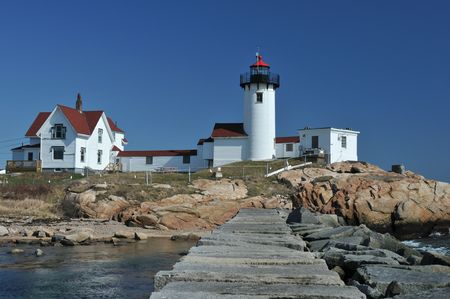 Eastern Point Lighthouse and breakwater, Gloucester, MA, on a clear spring day