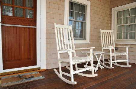 현관: 구식 흰 흔들 의자 앞 현관에 앉아 방문객을 환영합니다 스톡 사진