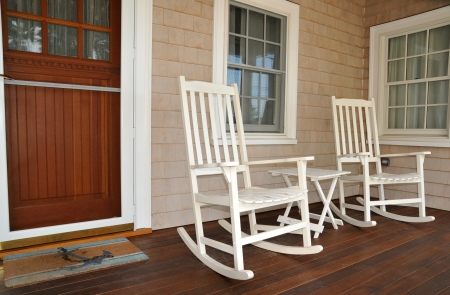 Old fashioned white rocking chairs welcome visitors to sit on the front porch photo