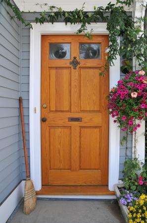 Voor deuropening versierd met bloemen en groen en schoongeveegd verwelkomt bezoekers
