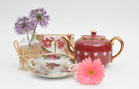 Still life arrangement of flowers, teapot, cup and saucer Imagens