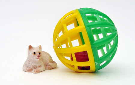 Miniature toy cat beside a cat toy