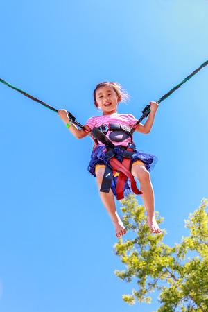 bungee jumping: Niña pasar un buen rato puenting en feria del condado.
