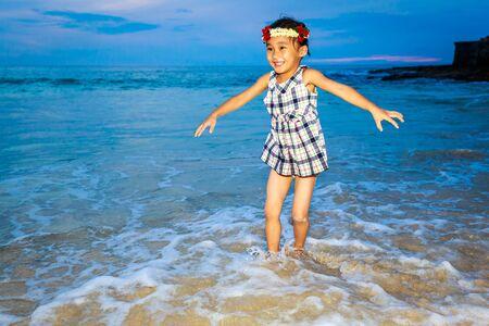 play time: Adorable girl enjoys play time on the beach. Stock Photo