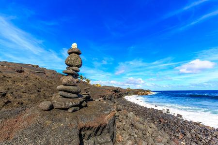 cairn: Black stone Cairn (ahu) at Kaimu beach park, Big Island, Hawaii.