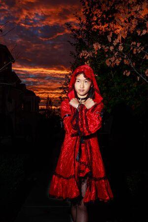 caperucita roja: Caperucita roja, que plantea en frente de la puesta de sol resplandor