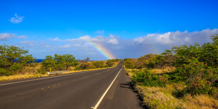 end of rainbow: Partial rainbow appears at the end of the highway road, under the sun.
