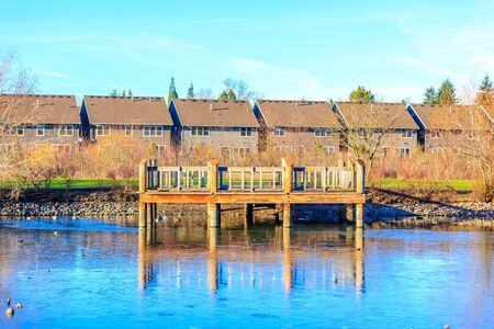 A small wooden deck at the lake shore with residence buildings in the back ground. Reklamní fotografie