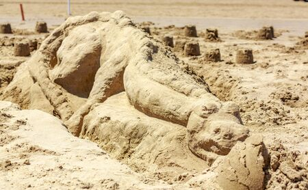 arts and entertainment: Sand sculpture of a dinosour lying on the ground of a digging site. Stock Photo