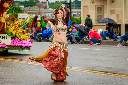 Portland, Oregon, USA - June 10, 2017: Persian style belly dancer in the Grand Floral Parade, as it stretched through the rain, during Portland Rose Festival 2017.