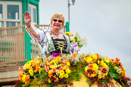 Portland, Oregon, USA - June 10, 2017: Leavenworth Autumn Leaf Festival Mini-Float, with Royal Lady Cindy Hassinger in the Grand Floral Parade, as it stretched through the rain, during Portland Rose Festival 2017.