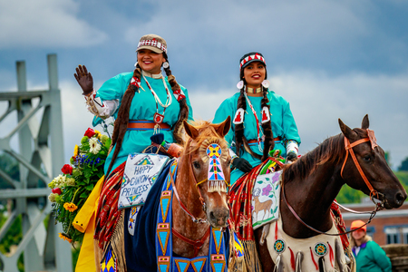 Portland, Oregon, USA - June 10, 2017: Royal Court of the Happy Canyon Indian Pageant, Princesses Gabriella Lewis and Virginia Conner  in the Grand Floral Parade, as it stretched through the rain, during Portland Rose Festival 2017.