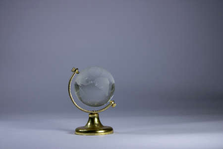 crystal globe on a table in white fade background