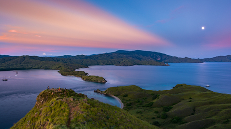 A Full Moon and A First Rays of Rising Sun in Pink Color At Gili Lawa with Clear Sky and Blue Sea. Komodo National Park, Labuan Bajo, Flores, Indonesia Imagens