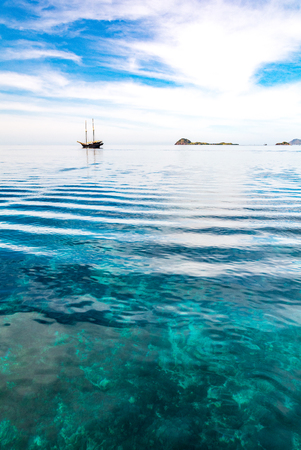 Transparent Deep Blue Sea with a Tourist Boat Background at Manta Point, Komodo National Park, Flores Island, Indonesia.