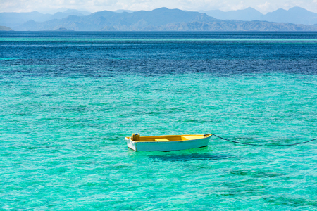 Floating Row Boat on Blue and Turquoise Clear Water with Mountain Background at Taka Makassar Island in Komodo National Park, Indonesia