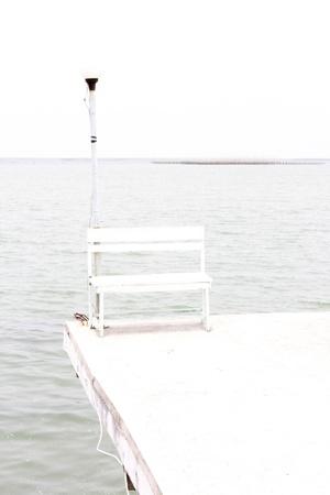 White bench near sea, white background photo