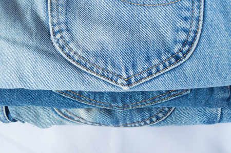 stack of blue jeans on white background Stock Photo