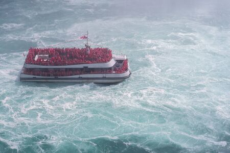 Boat approaching Niagara Falls with a crowd of people