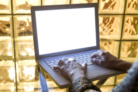 hands typing a letter in the keyboard of Stylish laptop computer with Isolated white screen.