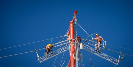 electricista: Trabajadores reparando una línea de energía eléctrica industrial de alta tensión. Grande para los temas de energía, seguridad y tecnología Editorial