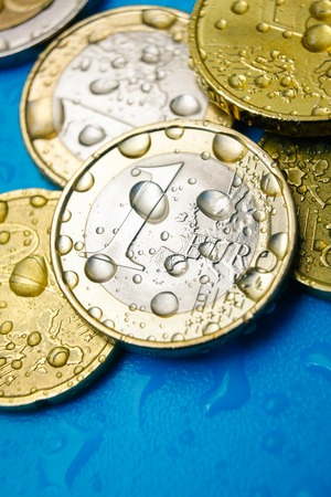 Water price concept with euro currency coins and water drops, vertical studio shot Stock Photo