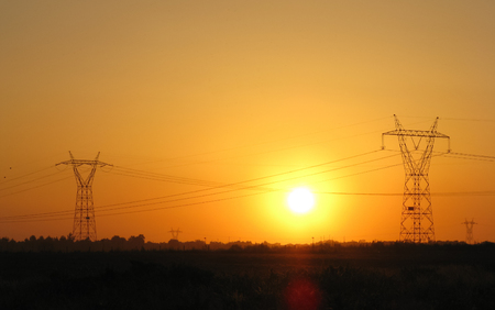 amp tower: High tension electrical power lines and pylon tower against sky. Modern industrial energy line. Sunset landscape Stock Photo