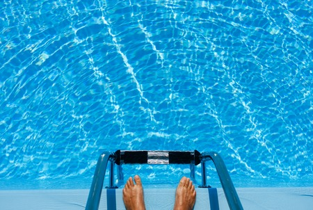 Hotel swimming pool with blue and sunny reflections, in a hot summer vacations.