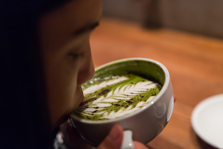 a girl is sipping the hot latte coffee in the morning Stock Photo