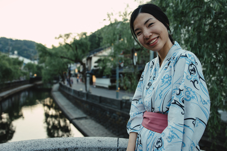 an asian girl smiling and wearing Yukata, Japanese traditional clothes, in old town with vintage color tone