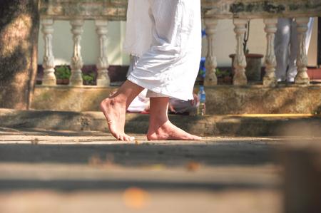 despacio: la persona en tela blanca está caminando lentamente a la meditación