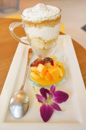 salad decoration: banoffee pie and fruit salad on dish with flower decoration in relax room
