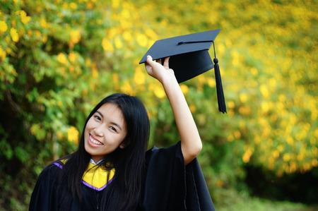 toga y birrete: Graduado feliz asi�tico de la Facultad de Ciencias en el campo del girasol mexicano, Tailandia