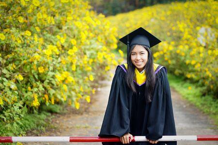 toga y birrete: graduado de la Facultad de Ciencias en el campo del girasol mexicano, Tailandia Foto de archivo