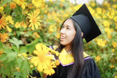 cap and gown: graduate from Faculty of Science at Mexican Sunflower field, Thailand Stock Photo