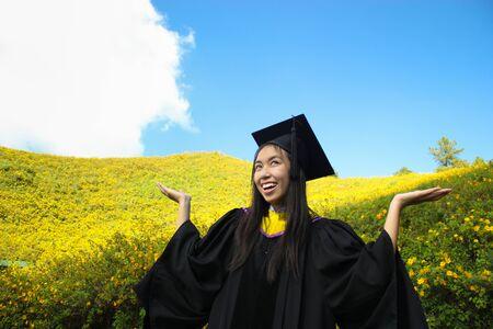 toga y birrete: asian happy graduate in Mexican Sunflower field Foto de archivo