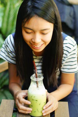 relax garden: girl drinking iced green tea in relax garden corner