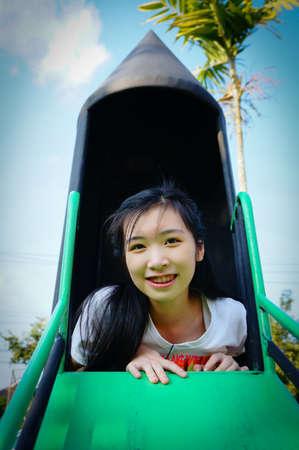 start play: girl start to play slider playground in park Stock Photo