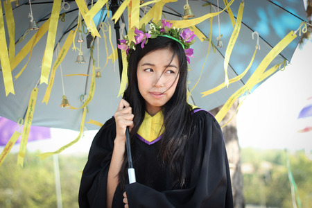 waiting posture: asian graduated girl with artificial flower crown and wish label on umbrella. Stock Photo