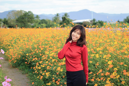 The Girl is happy to travel in colorful cosmos flower field at Muang Gan, Chiang mai city, Thailand Stock Photo