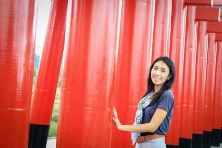 Woman travel at Hinoki land Chiang Mai, Thailand. New Attractions for travel far away from city. This place have beautiful red poles row, castle and garden resemble and same japanese culture style.