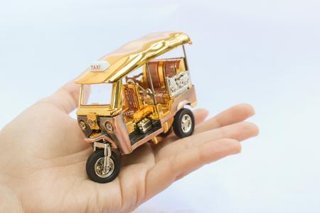Tuk Tuk - Thailand taxi model on hand on isolated white background