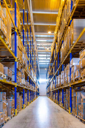 Interior of a modern warehouse storage with rows and goods boxes on high shelves Archivio Fotografico