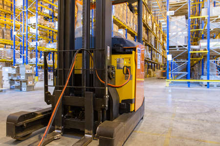 Electrical forklift loader charging in the warehouse. Pallet stacker truck equipment inside of a modern warehouse storage