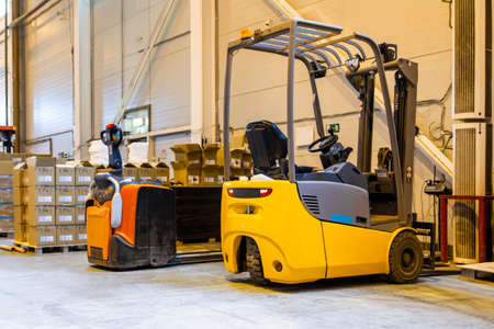 Forklift loader parking at logistics warehouse. Pallet stacker truck equipment inside of a modern warehouse storage Archivio Fotografico