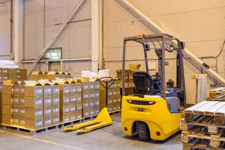 Forklift loader parking at logistics warehouse. Pallet stacker truck equipment inside of a modern warehouse storage