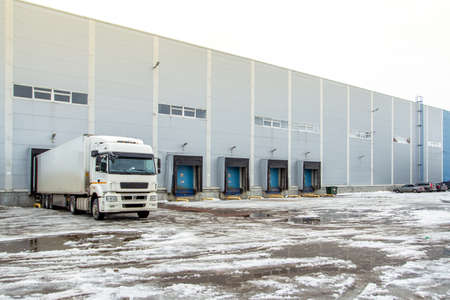 Truck while loading in a big distribution warehouse with gates for for loading goods and trucks